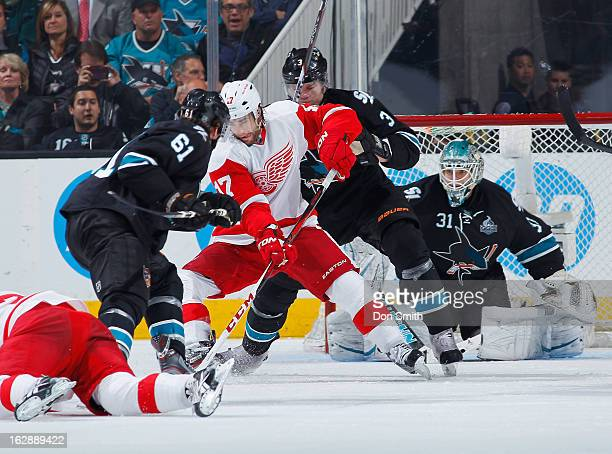 Justin Braun Douglas Murray and Antti Niemi of the San Jose Sharks protect the net against Patrick Eaves of the Detroit Red Wings during an NHL game...