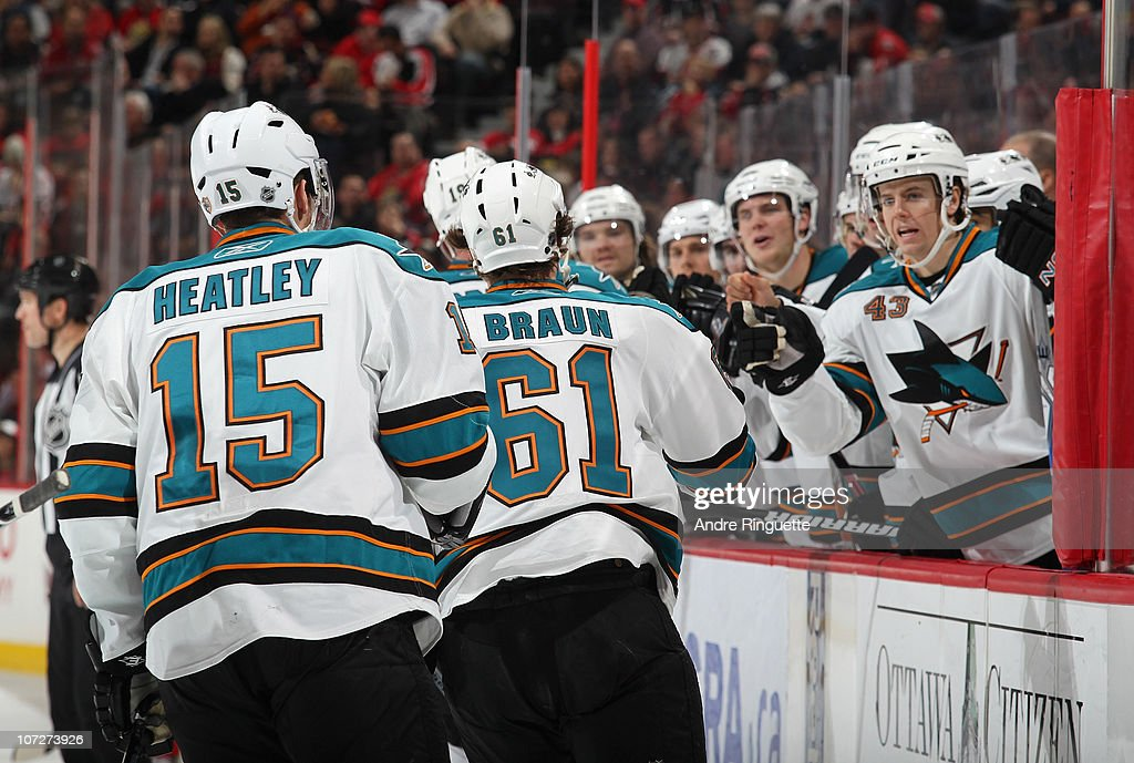 Justin Braun #61 of the San Jose Sharks celebrates his first career NHL goal with teammates Dany Heatley #15 and John McCarthy #43 at Scotiabank Place during an NHL game against the Ottawa Senators on December 2, 2010 in Ottawa, Ontario, Canada.