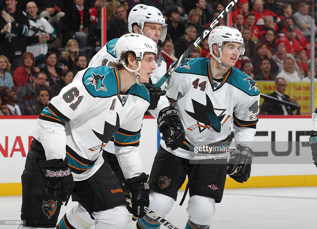 Justin Braun #61 of the San Jose Sharks celebrates his first career NHL goal with teammates Dany Heatley #15 and Marc-Edouard Vlasic #44 at Scotiabank Place during an NHL game against the Ottawa Senators on December 2, 2010 in Ottawa, Ontario, Canada.