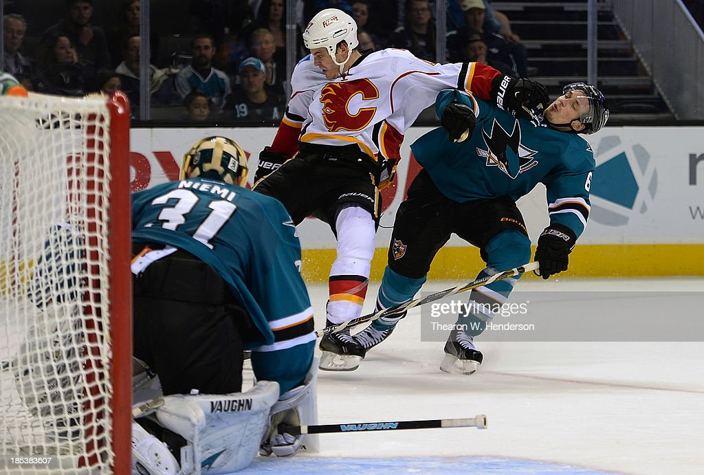 Justin Braun #61 of the San Jose Sharks collides with Lance Bouma #57 of the Calgary Flames during the third period at SAP Center on October 19, 2013 in San Jose, California.