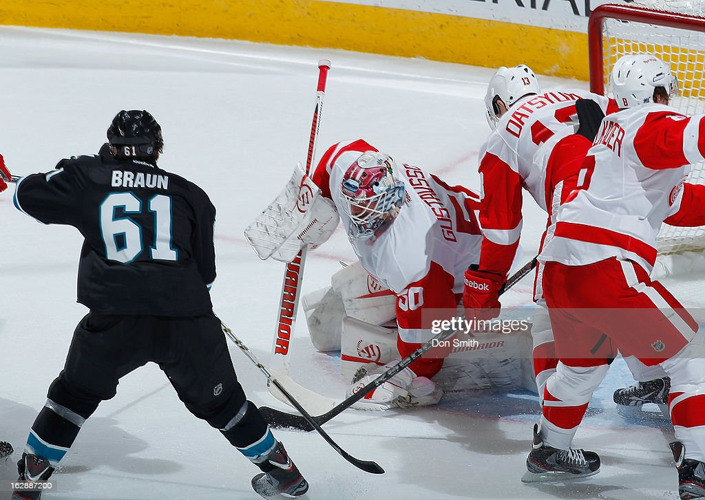 Justin Braun #61 of the San Jose Sharks looks for a rebound against Jonas Gustavsson #50 and Pavel Datsyuk #13 of the Detroit Red Wings during an NHL game on February 28, 2013 at HP Pavilion in San Jose, California.