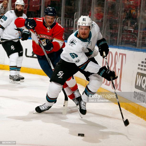 Justin Braun of the San Jose Sharks skates for possession against Jonathan Huberdeau of the Florida Panthers at the BBT Center on December 1 2017 in...