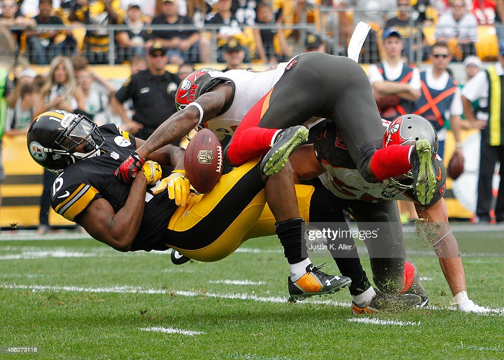 Justin Brown #15 of the Pittsburgh Steelers can't make a catch after being hit by Alterraun Verner #21 and Dane Fletcher #50 of the Tampa Bay Buccaneers during the first quarter at Heinz Field on September 28, 2014 in Pittsburgh, Pennsylvania.