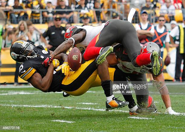 Justin Brown of the Pittsburgh Steelers can't make a catch after being hit by Alterraun Verner and Dane Fletcher of the Tampa Bay Buccaneers during...