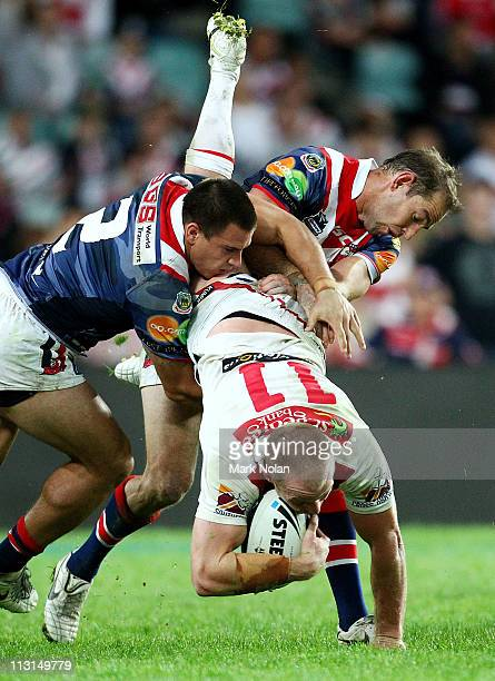 Justin Carney and Phil Graham of the Roosters tackle Beau Scott of the Dragons during the round seven NRL match between the Sydney Roosters and the...