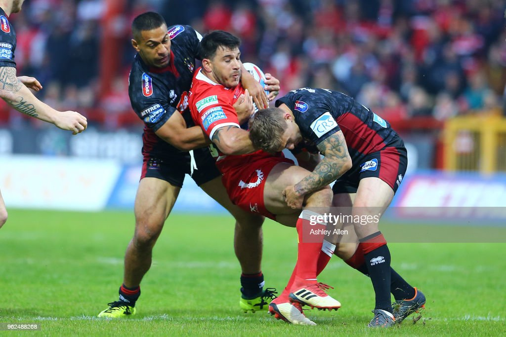 Justin Carney (C) of Hull KR is tackled by Sam Powell (R) and Willie Isa (L) of Wigan Warriors during the Betfred Super League at KCOM Craven Park on May 25, 2018 in Hull, England.