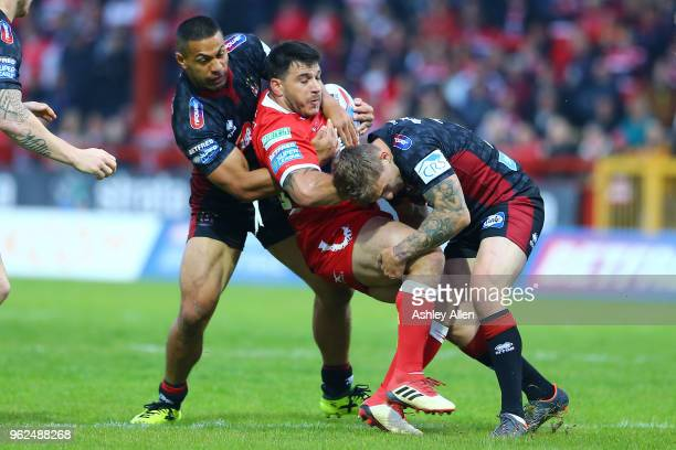 Justin Carney of Hull KR is tackled by Sam Powell and Willie Isa of Wigan Warriors during the Betfred Super League at KCOM Craven Park on May 25,...