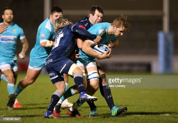 Justin Clegg of Worcester is tackled by Faf de Klerk and Josh Beaumont of Sale during the Gallagher Premiership Rugby match between Sale Sharks and...