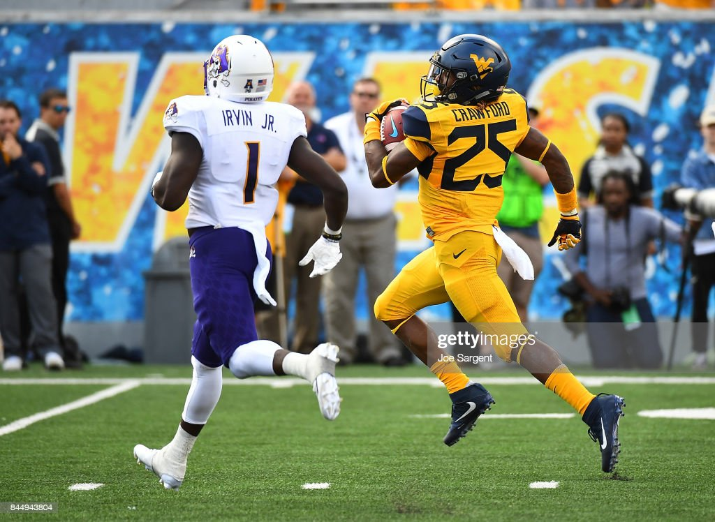 Justin Crawford #25 of the West Virginia Mountaineers runs for a touchdown in front of Tim Irvin #1 of the East Carolina Pirates during the second quarter at Mountaineer Field on September 9, 2017 in Morgantown, West Virginia.