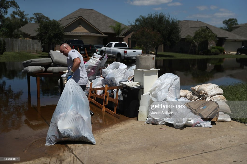 Justin Davison pulls a trash bag full of flood damaged items to a trash pile as he helps a friend clean out his flooded home on September 7, 2017 in Richwood, Texas. Over a week after Hurricane Harvey hit Southern Texas, residents are beginning the long process of recovering from the storm.