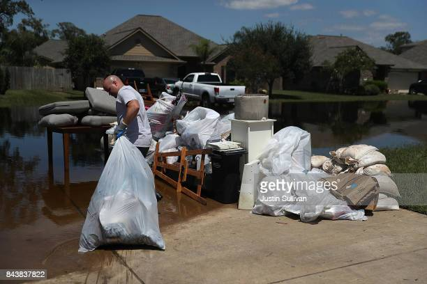 Justin Davison pulls a trash bag full of flood damaged items to a trash pile as he helps a friend clean out his flooded home on September 7 2017 in...