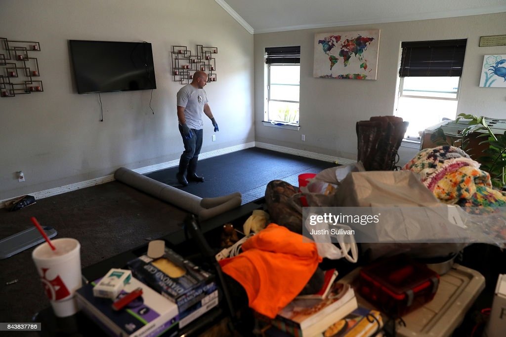 Justin Davison stands in the living room of his friend's flood damaged home on September 7, 2017 in Richwood, Texas. Over a week after Hurricane Harvey hit Southern Texas, residents are beginning the long process of recovering from the storm.