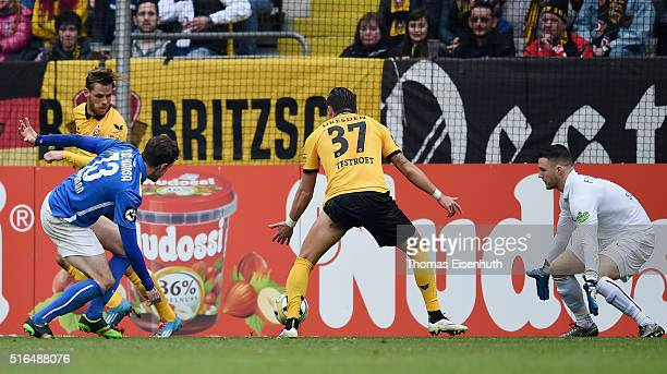 Justin Eilers of Dresden scores the opening goal against goalie Marcel Schuhen of Rostock during the Third League match between SG Dynamo Dresden and...