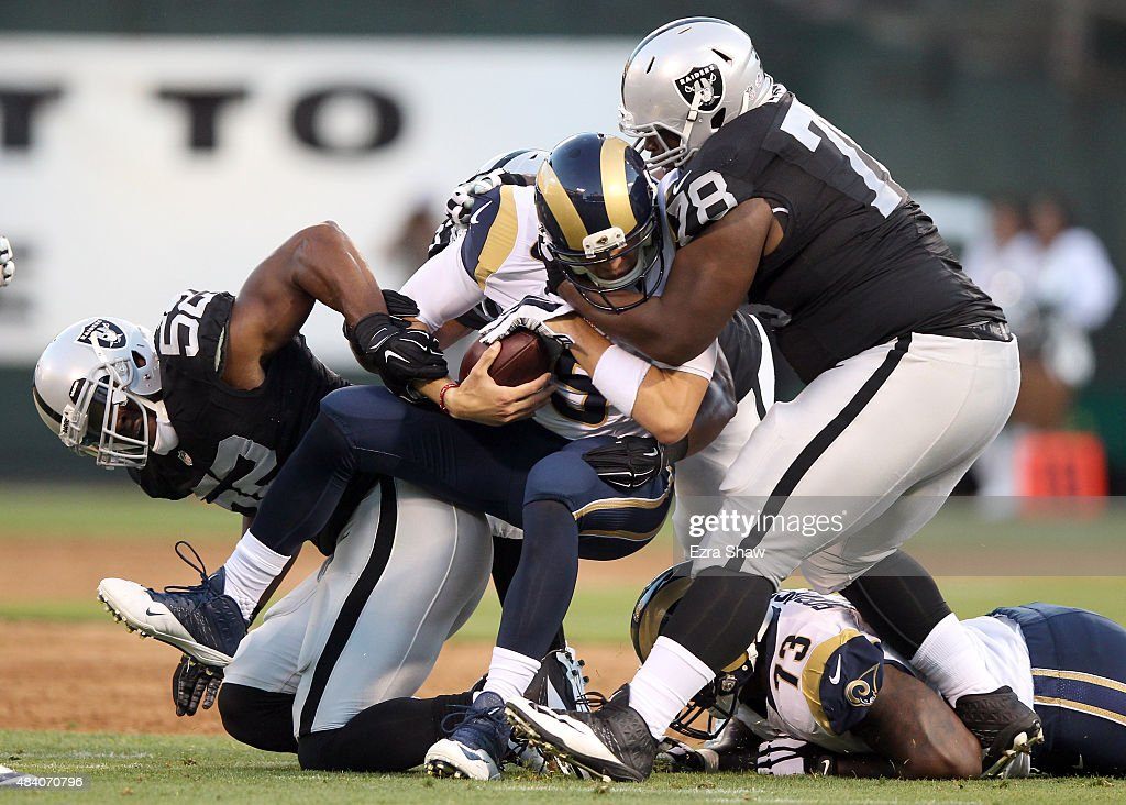 Justin Ellis #78, Malcolm Smith #53, and Khalil Mack #52 of the Oakland Raiders sack Nick Foles #5 of the St. Louis Rams at O.co Coliseum on August 14, 2015 in Oakland, California.
