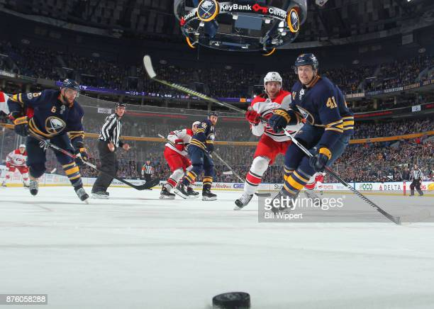 Justin Falk of the Buffalo Sabres battles for the puck against Elias Lindholm of the Carolina Hurricanes during an NHL game on November 18 2017 at...