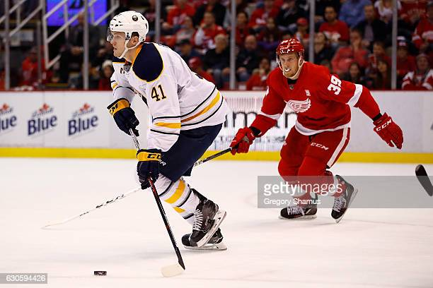 Justin Falk of the Buffalo Sabres looks for an open teammate as Anthony Mantha of the Detroit Red Wings pursues during the second period at Joe Louis...