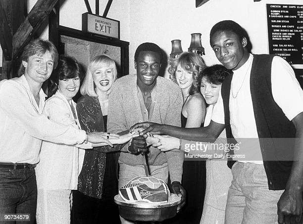 Justin Fashanu about to cut his birthday cake which is shaped like a football boot and football His brother John Fashanu is shown far right Justin...