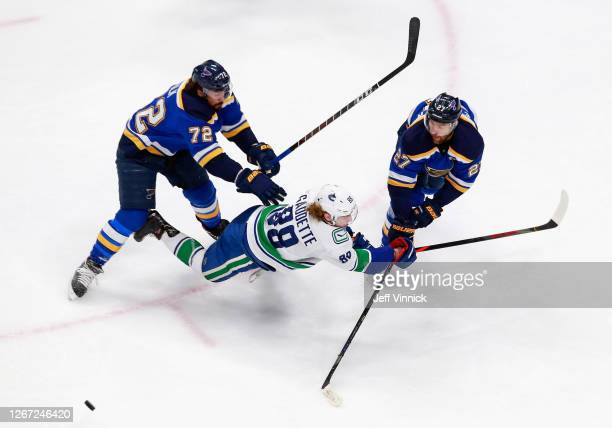 Justin Faulk and Alex Pietrangelo of the St. Louis Blues combine on Adam Gaudette of the Vancouver Canucks during the first period in Game Five of...