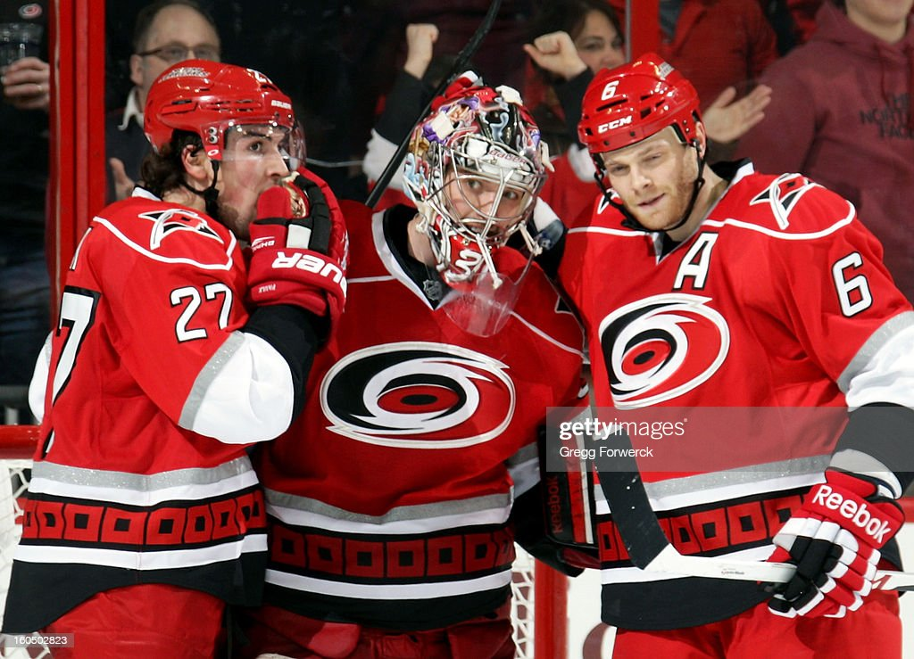 Justin Faulk #27 and Tim Gleason #6 of the Carolina Hurricanes congratulate Dan Ellis #31 following their shutout victory over the Ottawa Senators at PNC Arena on February 1, 2013 in Raleigh, North Carolina.