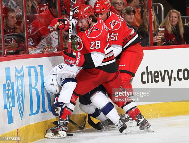 Justin Faulk and Tomas Kaberle of the Carolina Hurricanes get tagled up along the boards with Ryan Shannon of the Tampa Bay Lightning during a NHL...