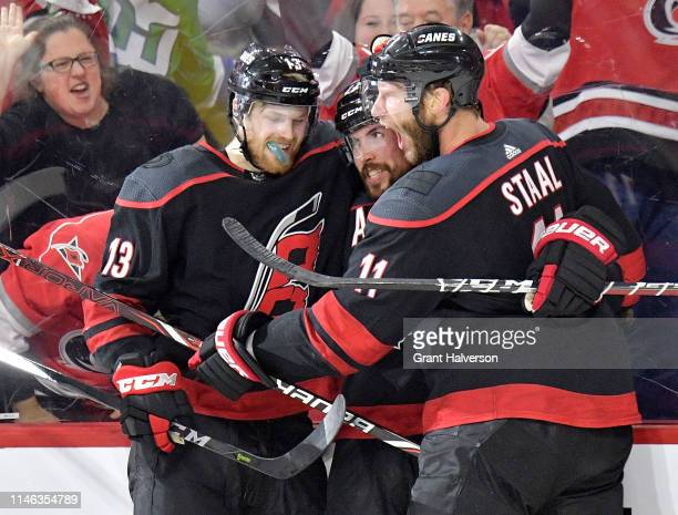 Justin Faulk celebrates with Warren Foegele and Jordan Staal of the Carolina Hurricanes after scoring against the New York Islanders during the...