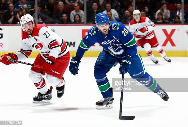 Justin Faulk of the Carolina Hurricanes and Brandon Sutter of the Vancouver Canucks skate up ice during their NHL game at Rogers Arena January 23,...