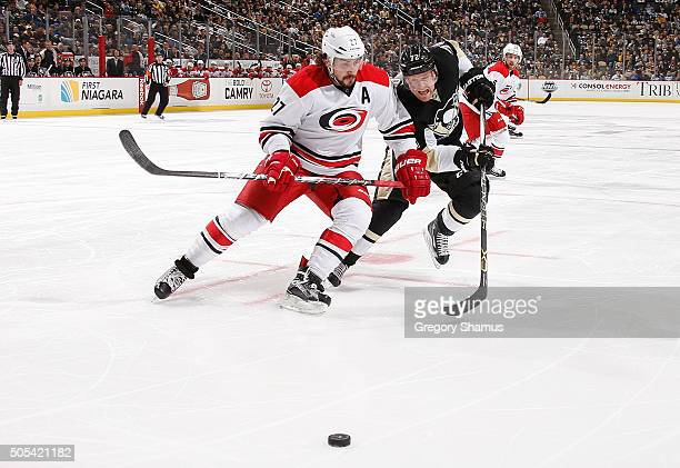 Justin Faulk of the Carolina Hurricanes and Patric Hornqvist of the Pittsburgh Penguins skate for the loose puck at Consol Energy Center on January...