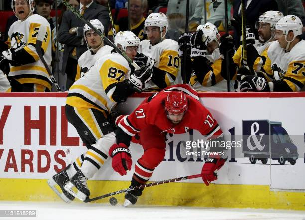 Justin Faulk of the Carolina Hurricanes and Sidney Crosby of the Pittsburgh Penguins get tangled up along the boards during an NHL game on March 19...