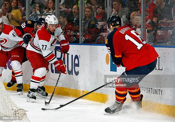Justin Faulk of the Carolina Hurricanes battles for the puck with Aleksander Barkov of the Florida Panthers during second period action at the BBT...