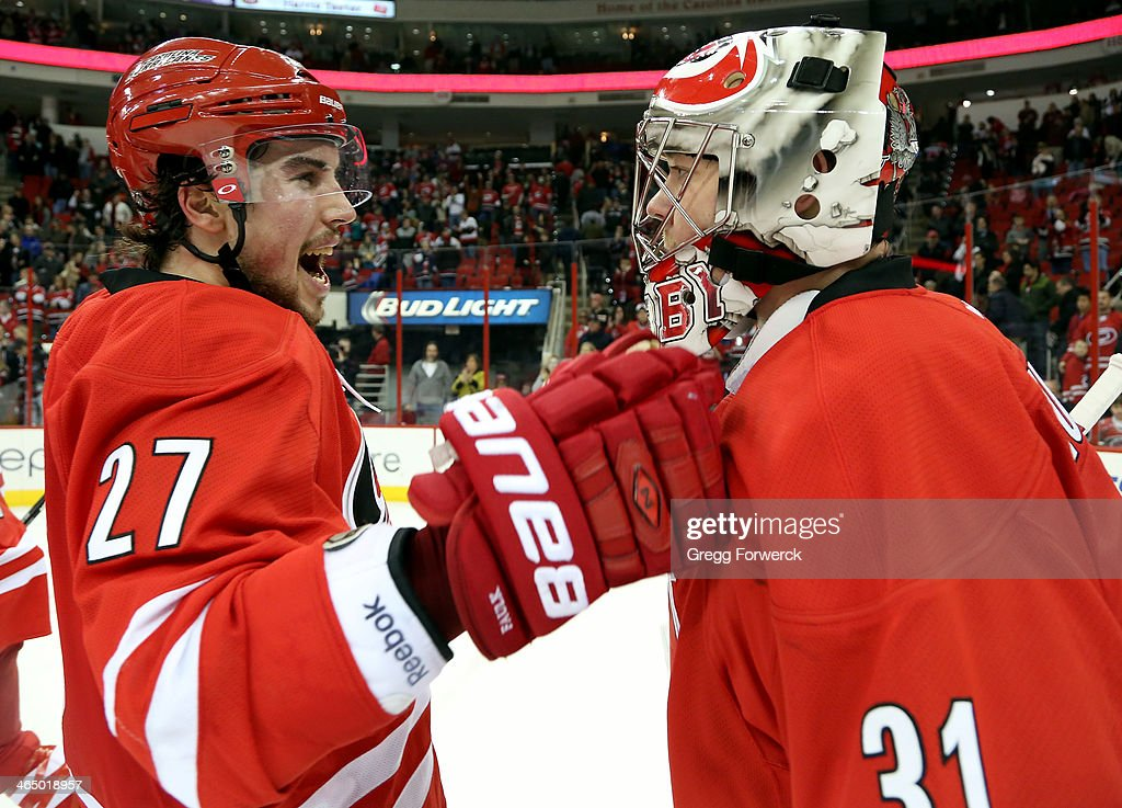 Justin Faulk #27 of the Carolina Hurricanes celebrates his team's 6-3 victory over the Ottawa Senators with winning goaltender Anton Khudobin #31 during their NHL game at PNC Arena on January 25, 2014 in Raleigh, North Carolina.