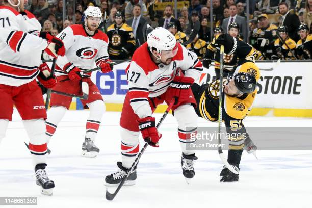 Justin Faulk of the Carolina Hurricanes checks Sean Kuraly of the Boston Bruins during the first period in Game Two of the Eastern Conference Final...