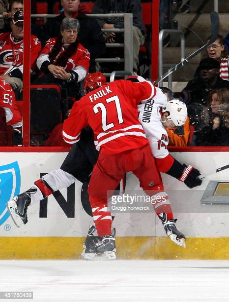Justin Faulk of the Carolina Hurricanes finishes a check on Colin Greening of the Ottawa Senators during their NHL game at PNC Arena on November 24...