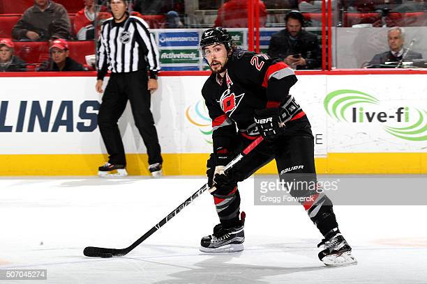 Justin Faulk of the Carolina Hurricanes looks to pass the puck during an NHL game against the Calgary Flames at PNC Arena on January 24 2016 in...