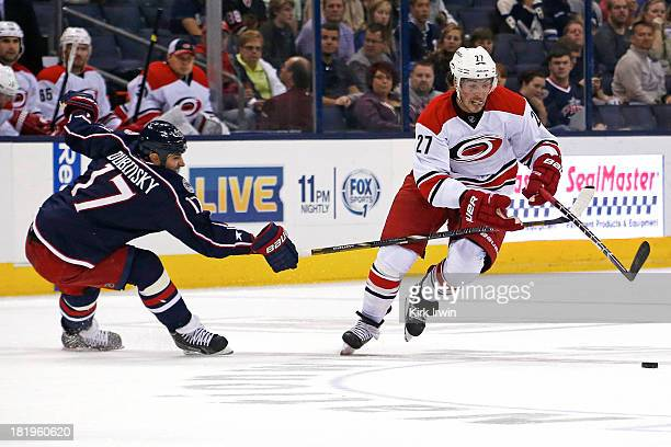 Justin Faulk of the Carolina Hurricanes skates the puck past Brandon Dubinsky of the Columbus Blue Jackets during the first period on September 26...