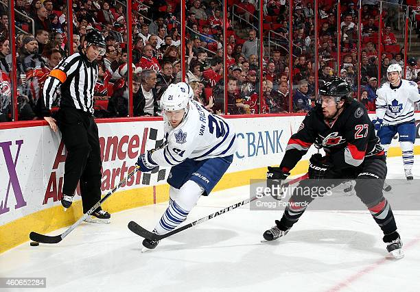 Justin Faulk of the Carolina Hurricanes stick checks James van Riemsdyk of the Toronto Maple Leafs as he moves the puck around the boards during...