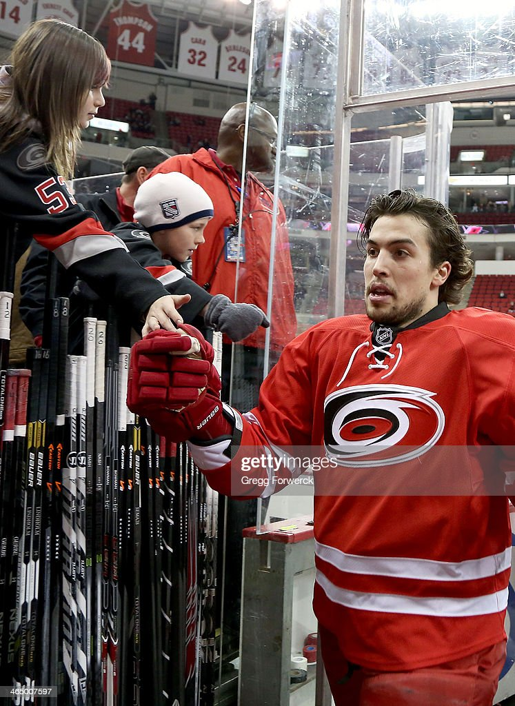 Justin Faulk #27 of the Carolina Hurricanes takes a moment to greet fans following warmups prior to an NHL game against the Ottawa Senators at PNC Arena on January 25, 2014 in Raleigh, North Carolina.