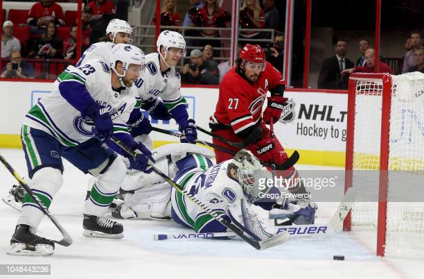 Justin Faulk of the Carolina Hurricanes takes a shot on goal as Jacob Markstrom of the Vancouver Canucks goes down in the crease and Alexander Edler...