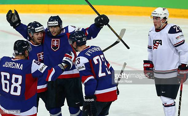 Justin Faulk of USA looks dejected while Tomas Zaborsky and Roman Kukumberg of Slovakia celebrate their 3rd during the IIHF World Championship group...