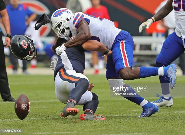 Justin Fields of the Chicago Bears is hit by Andre Smith of the Buffalo Bills during a preseason game at Soldier Field on August 21, 2021 in Chicago,...