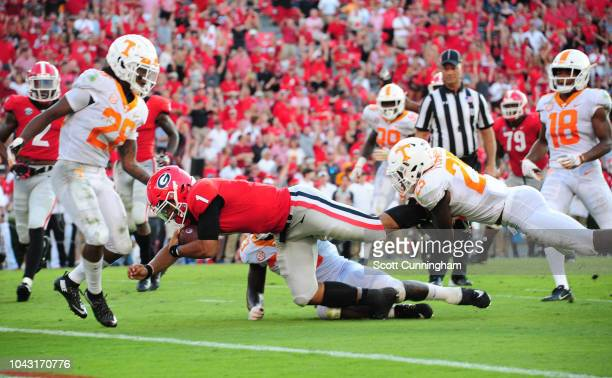Justin Fields of the Georgia Bulldogs carries the ball for a touchdown against the Tennessee Volunteers on September 29 2018 at Sanford Stadium in...