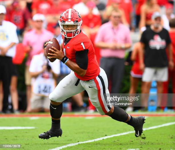 Justin Fields of the Georgia Bulldogs rolls out to pass against the Middle Tennessee Blue Raiders on September 15 2018 at Sanford Stadium in Athens...