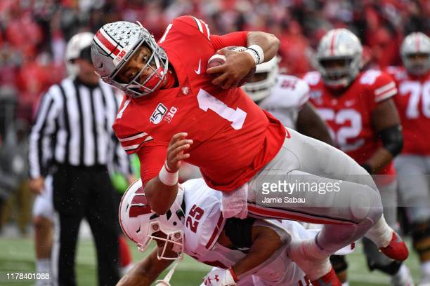 Justin Fields of the Ohio State Buckeyes dives over Eric Burrell of the Wisconsin Badgers in to the end zone on a 10yard touchdown run in the third...