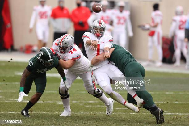 Justin Fields of the Ohio State Buckeyes gets a first half pass off while being tackled by Jacob Slade of the Michigan State Spartans at Spartan...