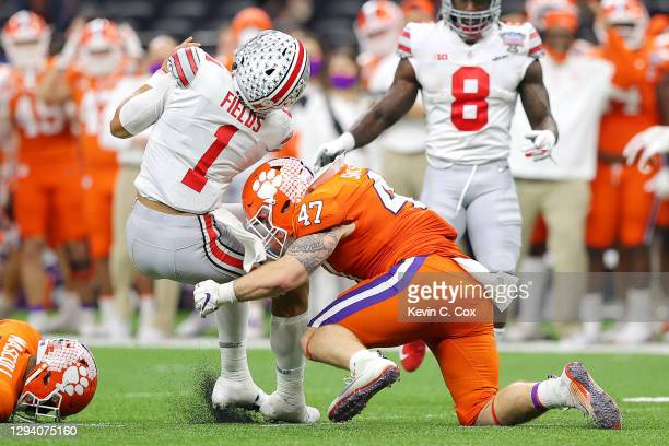 Justin Fields of the Ohio State Buckeyes is tackled by James Skalski of the Clemson Tigers in the second quarter during the College Football Playoff...
