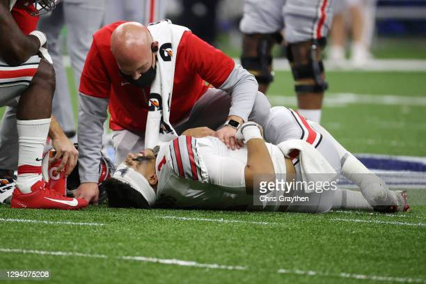 Justin Fields of the Ohio State Buckeyes is tended to by medical staff after sustaining an injury against the Clemson Tigers in the second quarter...