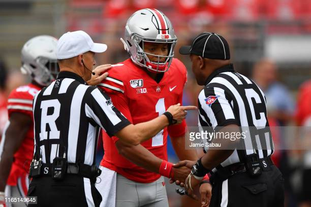 Justin Fields of the Ohio State Buckeyes meets with officials before a game against the Florida Atlantic Owls at Ohio Stadium on August 31 2019 in...
