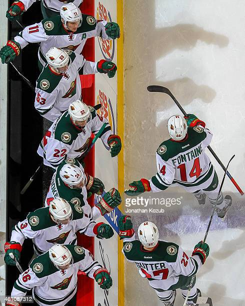 Justin Fontaine and Brett Sutter of the Minnesota Wild celebrate a second period goal against the Winnipeg Jets with teammates on December 29, 2014...