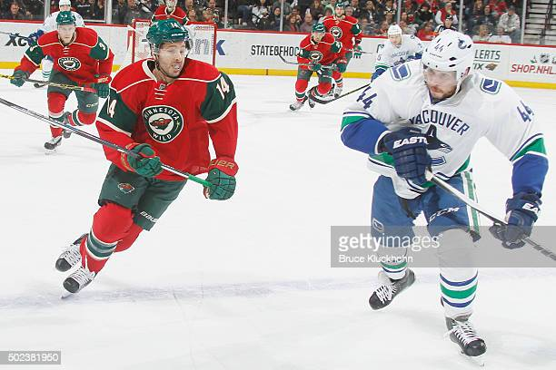 Justin Fontaine of the Minnesota Wild and Matt Bartkowski of the Vancouver Canucks skate to the puck during the game on December 15 2015 at the Xcel...