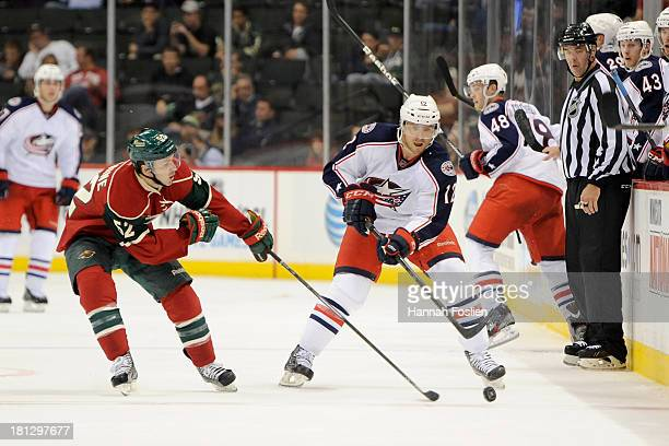 Justin Fontaine of the Minnesota Wild and Ryan Craig of the Columbus Blue Jackets go after the puck during the preseason game on September 17 2013 at...