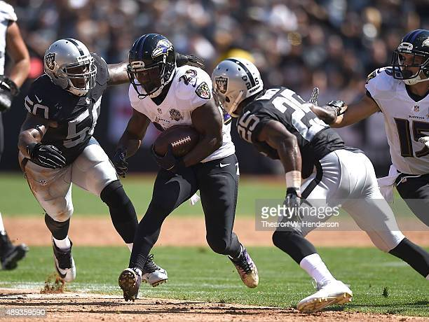 Justin Forsett of the Baltimore Ravens runs through the block of Curtis Lofton of the Oakland Raiders and D.J. Hayden of the Oakland Raiders in the...
